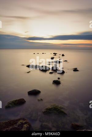 Seascape de mer soyeuse avec des pierres contre un ciel coloré au lever du soleil . Banque D'Images