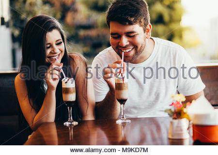 Jeune couple amoureux assis dans un café, boire du café, avoir une conversation et d'apprécier le temps passé avec chaque autre Banque D'Images