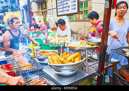 YANGON, MYANMAR - février 14, 2018: des stands de nourriture de rue et de petits cafés en plein air sont très populaires dans le quartier chinois, les cuisiniers locaux offrent des légumes, viandes épicées Banque D'Images