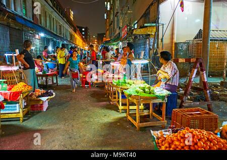 YANGON, MYANMAR - février 14, 2018: La rue étroite du quartier chinois est utilisé par les nombreux étals de marché alimentaire, plein de fruits et légumes frais Banque D'Images