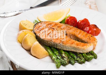 Tranche de saumon grillé garni de pommes de terre cuites, asperges vertes, tomates cerise et citron au cari Banque D'Images