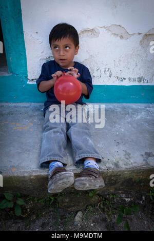 Jeune garçon maya joue avec un ballon rouge sur les marches de sa maison au Guatemala Banque D'Images