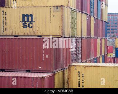 Les conteneurs d'expédition colorés empilés haut: les conteneurs d'expédition normalisées empilés dans le port de Montréal, à côté de la voie ferrée. Banque D'Images
