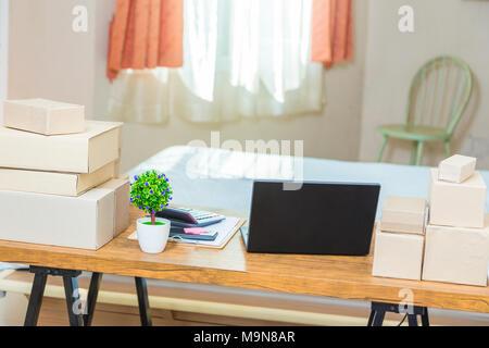Home Office, et une chambre à coucher, de jeunes entreprises en ligne indépendant du vendeur, montrant la table de bureau avec ordinateur portable, les boîtes de produits Banque D'Images