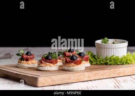 De délicieux canapés au salami, des olives et d'épices sur un fond boisé Banque D'Images