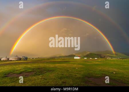 Double arc-en-ciel au-dessus de yourtes nomades dans un paysage verdoyant, la Mongolie Banque D'Images