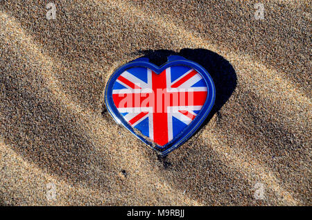 Une Union jack le couvert d'un étain en forme de cœur allongé sur une plage à motifs de sable. Banque D'Images