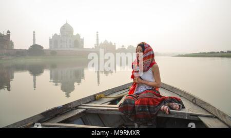 Une femme regardant le coucher du soleil sur le Taj Mahal à partir d'un bateau en bois. Banque D'Images