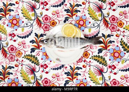 Un serran avec la poupée de l'œil à l'intérieur d'une plaque fleur cachée sur un tissu fleuri. Jeu du camouflage. Couleur minimum still life la photographie. Banque D'Images