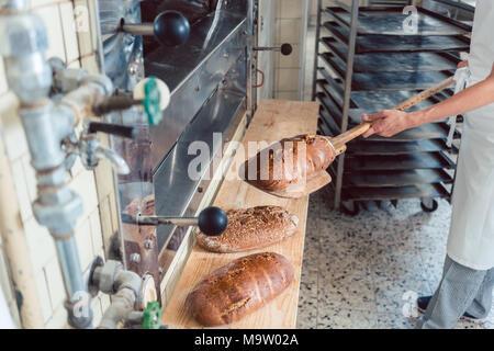 Femme de mettre du pain de boulangerie à bord Banque D'Images