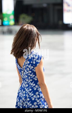 Vue arrière d'une femme en robe à fleurs flou de marcher dans la rue Banque D'Images