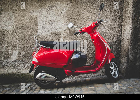 Vintage scooter rouge garée devant un mur gris à Thoune en Suisse Banque D'Images