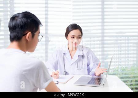 Friendly female doctor mains tenant la main du patient assis au bureau Banque D'Images