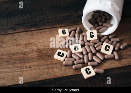 La vitamine C comprimés et la bouteille sur table en bois avec des carreaux alphabet lettre écrite C. Santé concept Banque D'Images