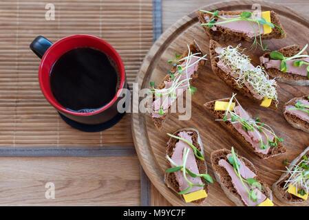 Les sandwiches avec micro verts et la tasse de café du matin. Parti Vegan tableau des aliments avec des légumes biologiques des canapés. Mode de vie sain, ingrédients de cuisine moderne et bien manger concept. Banque D'Images