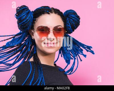 Close-up of woman with pigtails bleu tête tressé African girl with blue tresses, coiffure. Portrait Hipster girl with sunglasses sur fond coloré. Concept de vie.