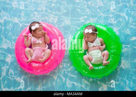 La semaine deux sœurs jumeaux de bébé dormir sur de minuscules, gonflables, anneaux de bain rose et vert. Ils portent des maillots en bonneterie. Banque D'Images