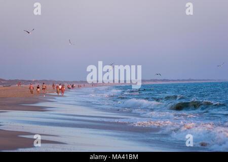 Les gens qui marchent pendant le coucher du soleil à la plage de Matalascañas, Almonte, Province de Huelva, Andalousie, espagne. Banque D'Images