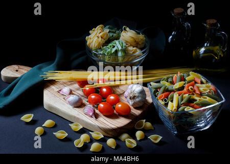 Ingrédients Pâtes alimentaires sombre clair-obscur avec des spaghetti, tagliatelle et penne tricolore et l'ail avec de l'huile d'olive with copy space Banque D'Images