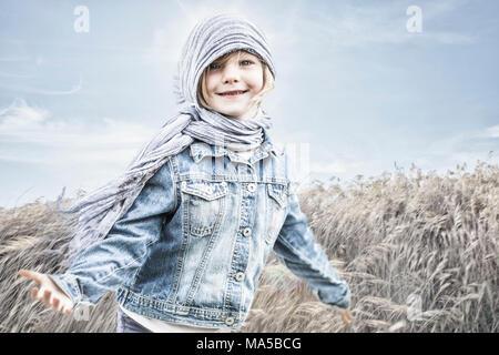 Petite fille debout dans un champ, contre le vent Banque D'Images