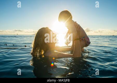 Femme jouant avec son petit bébé dans une piscine au coucher du soleil, Papeete, Tahiti, Polynésie Française Banque D'Images