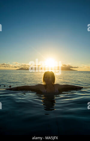Femme pour le coucher du soleil dans une piscine, Papeete, Tahiti, Polynésie Française Banque D'Images