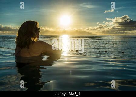 Femme pour le coucher du soleil dans une piscine avec Moorea en arrière-plan, Papeete, Tahiti, Polynésie Française Banque D'Images