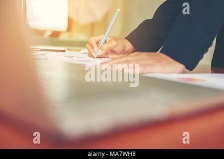 Mains de femme d'affaires gestionnaire financier en prenant des notes quand on travaille sur le rapport. Banque D'Images