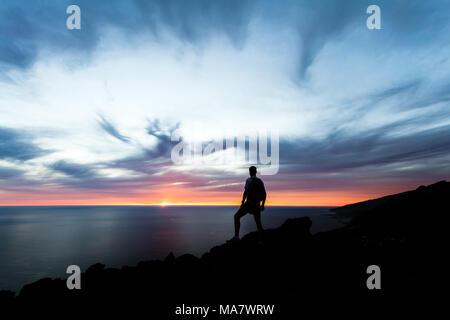 Célébrer ou méditer l'homme à la mer au coucher du soleil. Sac à dos de randonneur avec le sommet de la montagne à la recherche d'inspiration dans le magnifique paysage de nuit. Banque D'Images