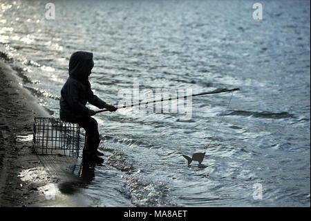 Un garçon de cinq ans est la pêche au lac. Banque D'Images