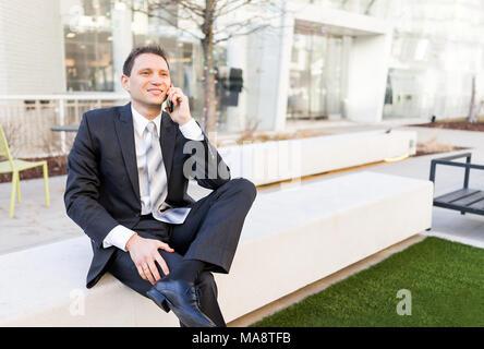 Beau, beau jeune homme assis sur un banc, à l'aide de parler holding smartphone téléphone téléphone mobile cellphone smiling in costume, cravate, joyeux sur Banque D'Images