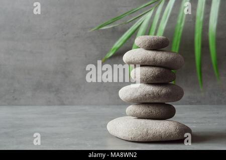 Des pierres et des feuilles de palmier vert l'équilibre. Concept spa et zen. Banque D'Images