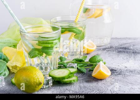 Les agrumes et les herbes de l'eau infusée sassi pour désintoxication, la saine alimentation dans les verres et verseuse sur sur fond sombre Banque D'Images