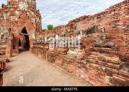 Les broken statues de Bouddha sur l'ancien mur de briques en Wat Chaiwatthanaram temple bouddhiste dans la ville d'Ayutthaya Historical Park à Ayutthaya, Thaïlande Banque D'Images