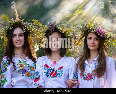 Uzhgorod, Ukraine - 07 juil 2016: Portraits de trois jeunes femmes avec couronne traditionnelles sur leurs têtes. contexte du parc avec la lumière venant par Banque D'Images