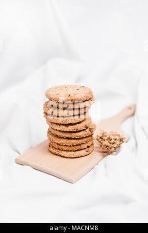 Des biscuits sucrés sur une planche en bois et fond blanc Banque D'Images