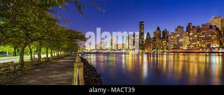 Vue panoramique sur les gratte-ciel de Manhattan et l'East River, au crépuscule de Roosevelt Island, promenade en été. New York City Banque D'Images