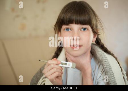 Petite fille en rose peignoir holding un thermomètre numérique à haute température, close-up shot Banque D'Images