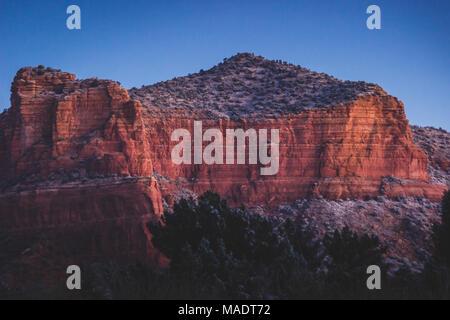 Des formations de roche rouge couverte de plaques de neige au lever du soleil avec un ciel clair, Coconino National Forest, Arizona Banque D'Images