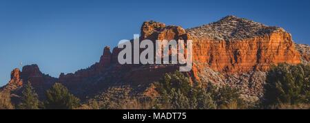 Des formations de roche rouge couverte de plaques de neige au lever du soleil avec un ciel clair et un ballon à air chaud dans la distance, Coconino National Forest, Arizona Banque D'Images