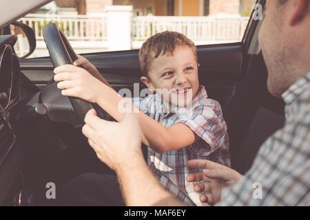 Heureux père et fils assis dans la voiture à la journée. Les gens se préparer pour road trip. Concept de famille heureuse.