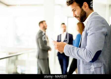 Handsome young businessman using mobile phone in office
