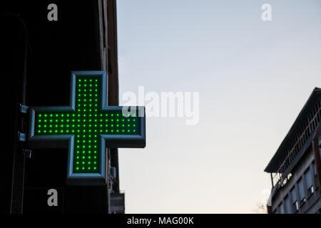 Pharmacie la croix verte allumée avec le néon et la LED s'allume dans le coucher du soleil. Cette croix est un symbole universel pour la pharmacie en Europe Photo d'une croix verte indiquent Banque D'Images