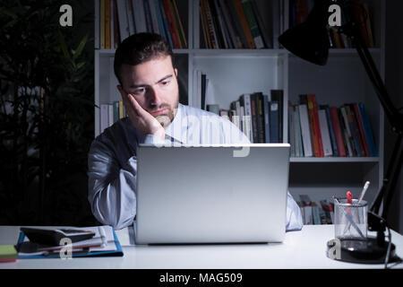 Businessman face portrait travaillant au sein de l'office de nuit Banque D'Images