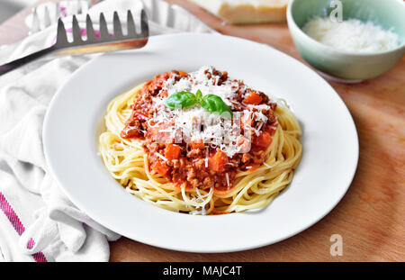Repas délicieux plats de pâtes, spaghettis à la bolognaise sur une plaque blanche. Plat de pâtes, cuisine italienne traditionnelle avec le parmesan, les viandes hachées et feuille de basilic. Banque D'Images