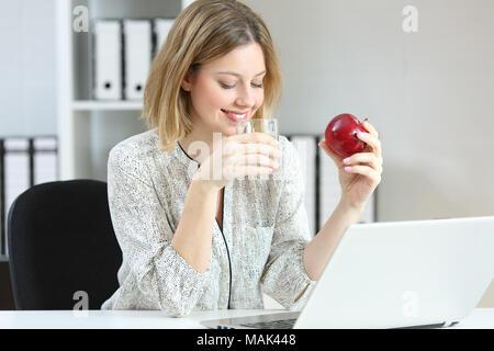 Office worker eau potable d'un verre et manger une pomme sur un bureau Banque D'Images
