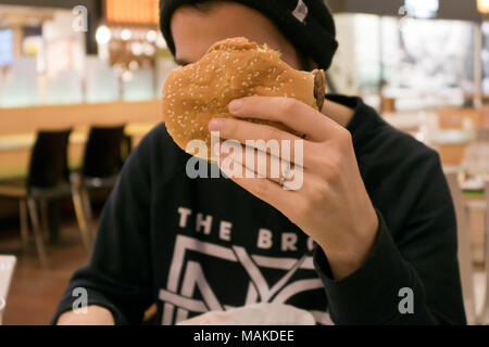 Young man eating hamburger Banque D'Images