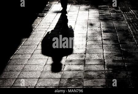 Ombre floue et silhouette d'un homme debout, dans la nuit, sur le trottoir de la rue ville humide avec de l'eau reflet en noir et blanc Banque D'Images
