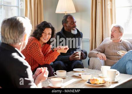 Groupe d'amis d'âge moyen autour de Réunion Table Dans Coffee Shop Banque D'Images