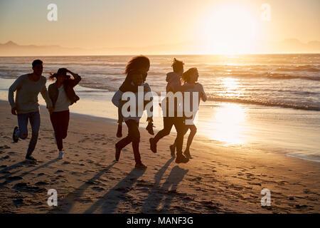 Silhouette d'amis s'amuser le long de la plage d'hiver Banque D'Images